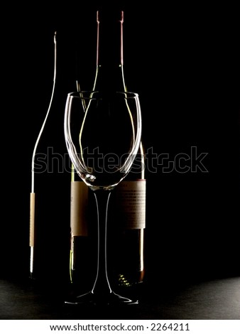 Two bottles of wine and a glass against a black background.