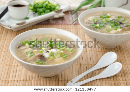 two bowls of chinese spicy soup with egg, shiitake mushrooms, tofu and green onions