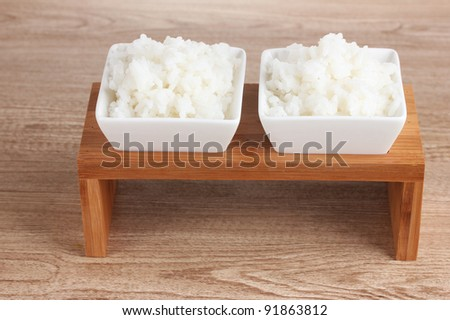 Two bowls of cooked rice on wooden table