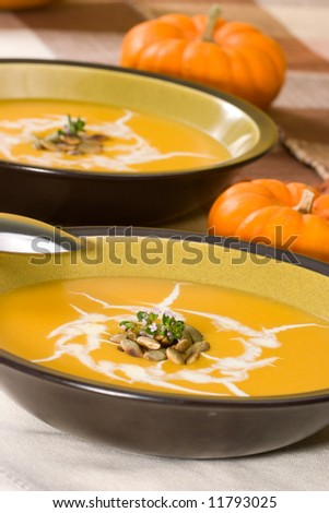 Two bowls of hot delicious pumpkin soup garnished with cream, roasted pumpkin seeds and fresh thyme