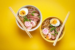 Two bowls of Japanese noodle soup ramen with meat broth, sliced pork, narutomaki, egg with yolk on pastel yellow background. Traditional dish of Japan, top view, close-up, concept