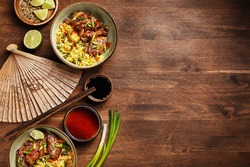 Two bowls of pan asian style chicken wings in teriyaki sauce with sesame seeds, rice and vegetables on wooden aged background with wooden fan, lime, chives, chopsticks and sauces. Top view, copy space