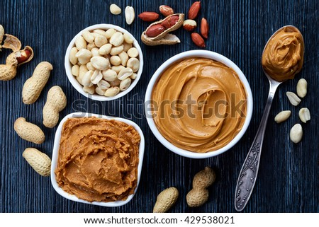 Two bowls of peanut butter and peanuts on dark wooden background from top view Stock photo ©