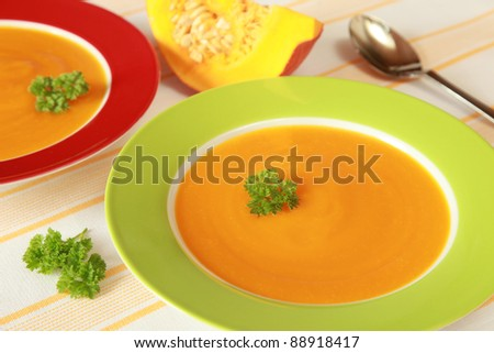 Two Bowls of pumpkin soup and a pumpkin in the background - stock photo