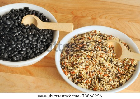 Two bowls on a cutting board containing uncooked wild rice and black beans