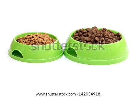 Two bowls with dry food for dog or cat isolated on white background