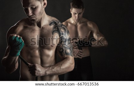 Two boxer are putting on straps preparing for combat on a dark background