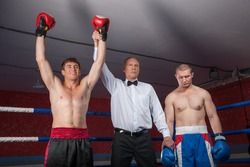 two boxer men standing in ring. referee lifting winner hand announcing victory