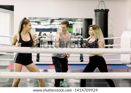 2d0147517 Two boxer women greet each other before fight, their young handsome trainer  is standing between
