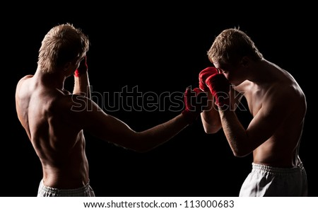 two boxers are fighting over dark background