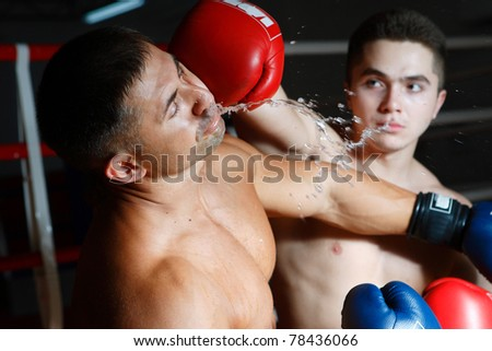 Two boxers battle on a ring one beats another in the person a glove