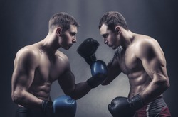 Two boxers in boxing gloves met with glances against a dark background