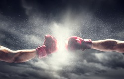 Two boxing gloves punch. Light on cloudy sky. Box, power, fight symbols.