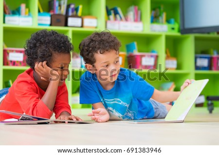 Two boy kid lay down on floor and reading tale book  in preschool library,Kindergarten school education concept