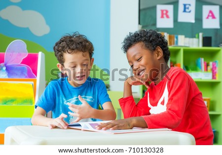 Shutterstock Two boy kid sit on table and reading tale book  in preschool library,Kindergarten school education concept,children day card