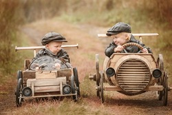 Two boy racer at the start on makeshift wooden machines compete on the rural outskirts