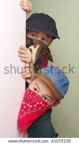 Two boys ages eight and six years, wearing bandit masks, sneak and peek around a corner