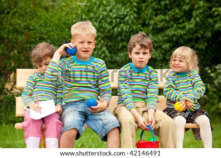 Two boys and two girls on a bench in park. In identical stripe clothes.