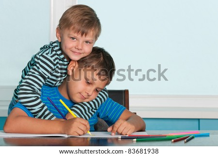 Two boys are sitting at the desk and drawing