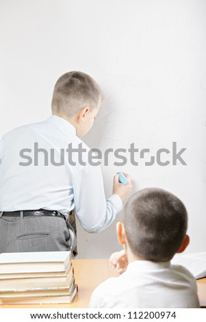 Two boys at whiteboard one writing while other sitting