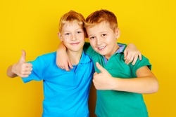 Two boys best friends standing together. Bright yellow background. Summer fashion.
