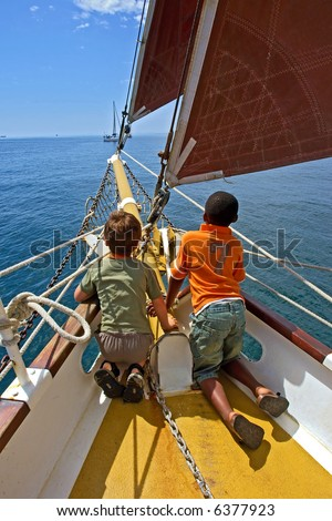 Two boys, black and white, play on yacht's deck. Shot during yacht cruise in Waterfront, Cape Town, South Africa.