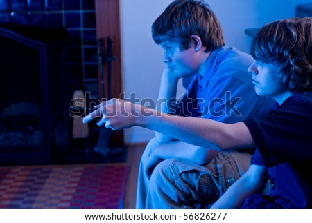 Two boys (brothers) watching TV, bored and channel surfing - stock photo
