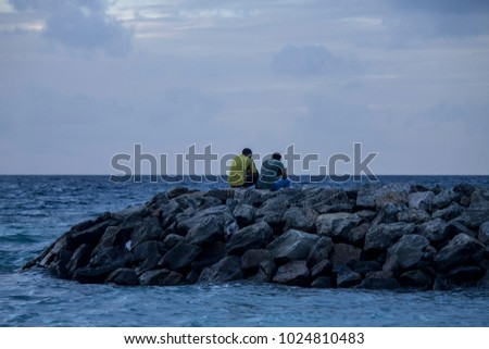Two boys contemplating the sea from the rocks in Maafushi, Maldives