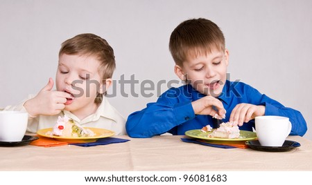 two boys eating a cake his hands