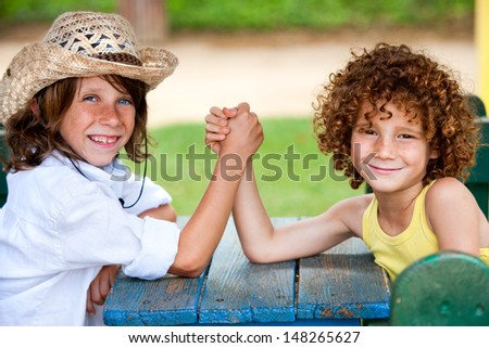 Two boys having arm wrestle in park.