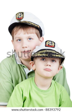 Two boys in green T-shirts and white sea peak-caps with eyes looking somewhere upward, focus on little boy - stock photo