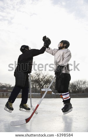 Two boys in ice hockey uniforms giving eachother high five on ice rink.