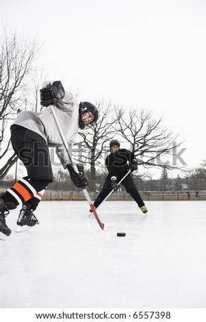 Two boys in ice hockey uniforms skating on ice rink moving puck.