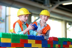 Two boys in safety helmets and high visibility jackets playing indoors. Schoolchildren building with construction bricks. Safety education for young kids. Playful work experience for future engineers.