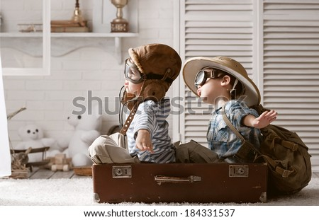 Two boys in the form of an aircraft pilot and traveler playing in her room