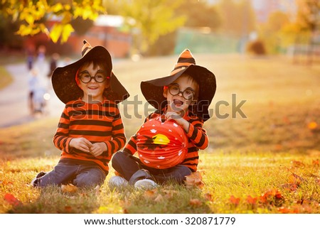 Two boys in the park with Halloween costumes, having fun
