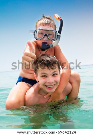Two boys in the sea on a beach