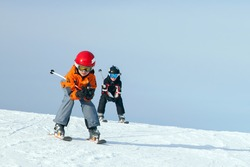 Two boys is skiing at ski lesson in winter day