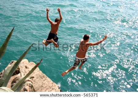 Two boys jumping into water from a rock