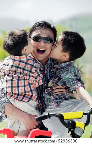 Two boys kissing their father's cheeks while he holds them in his arms