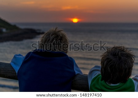 two boys looking at a beautiful sunset