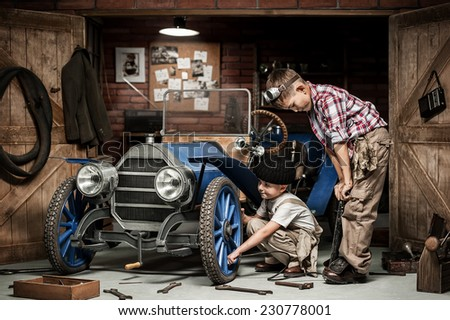stock photo two boys mechanical inflated tire on the retro car in the garage 230778001 - Каталог — Фотообои «Ретро»