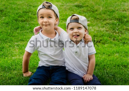 Two boys of three years in white T-shirts, jeans and caps are sitting on the grass and hugging. Two close friends, two cousins. Family relations between brothers