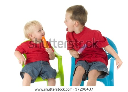 Two boys on lawn chairs enjoying popsicles