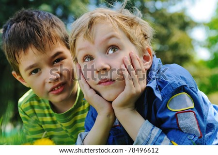 Two boys on the green grass in the park