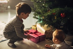 Two boys picking up christmas gifts from under the Christmas tree. Christmas gifts placed beside a Christmas tree with two kids.