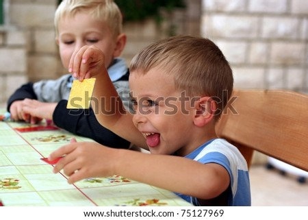 Two boys play a board game, one boy shows a card
