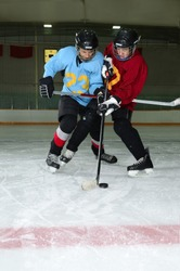 Two Boys play a Winter Hockey Scrimmage in Rink