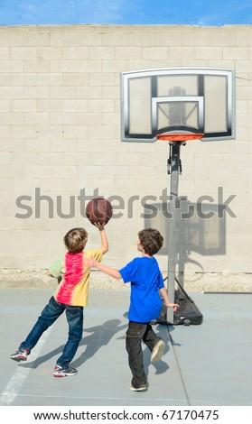Two boys play basketball
