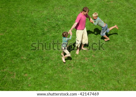 Two boys play with the adult a lawn. The top view.